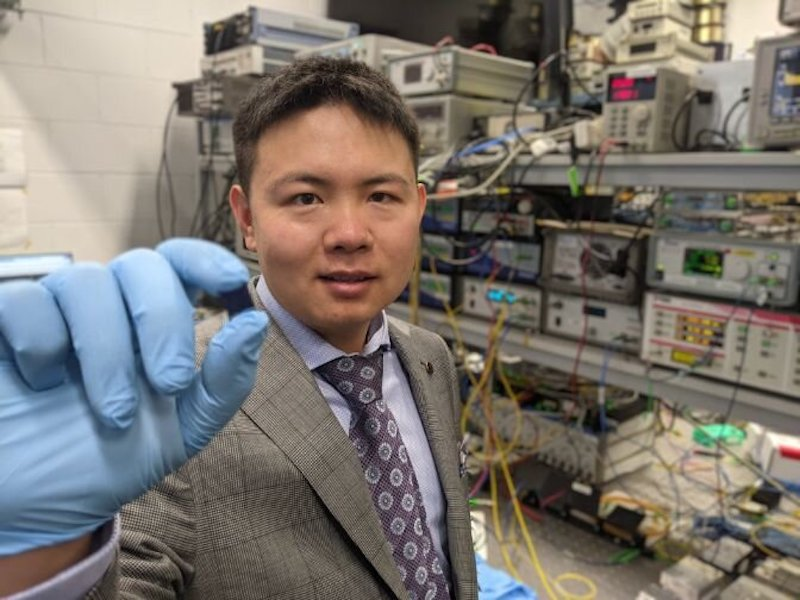 Dr Xingyuan (Mike) Xu with the integrated optical microcomb chip, which forms the core part of the optical neuromorphic processor. Credit: Swinburne University of Technology